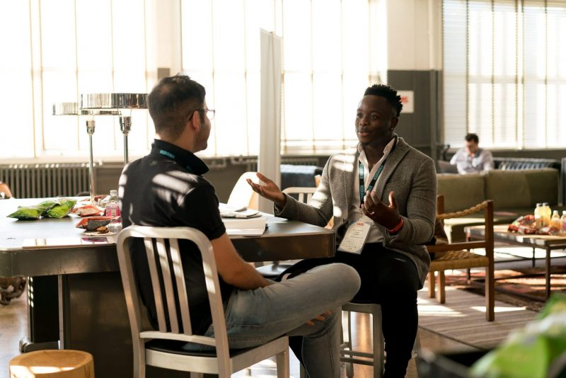 two men talking in hotel lobby | better conversations