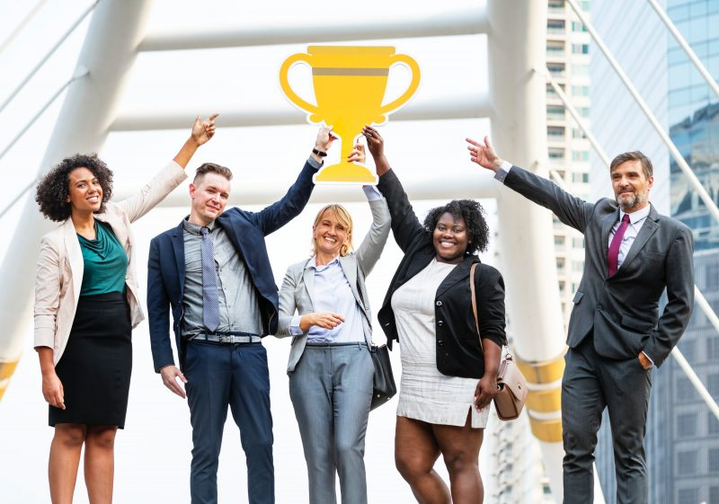 coworkers raising a cutout trophy | thought leadership