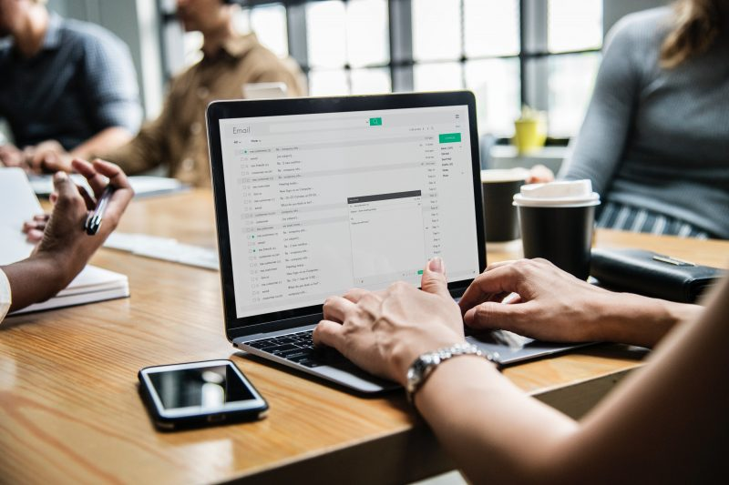 woman typing during team meeting | email marketing list