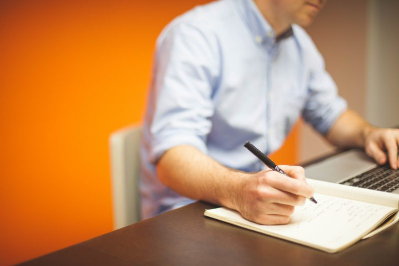 man taking notes while working on Mac | copywriting myths