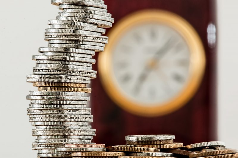 stack of coins with clock in background | marketing budget