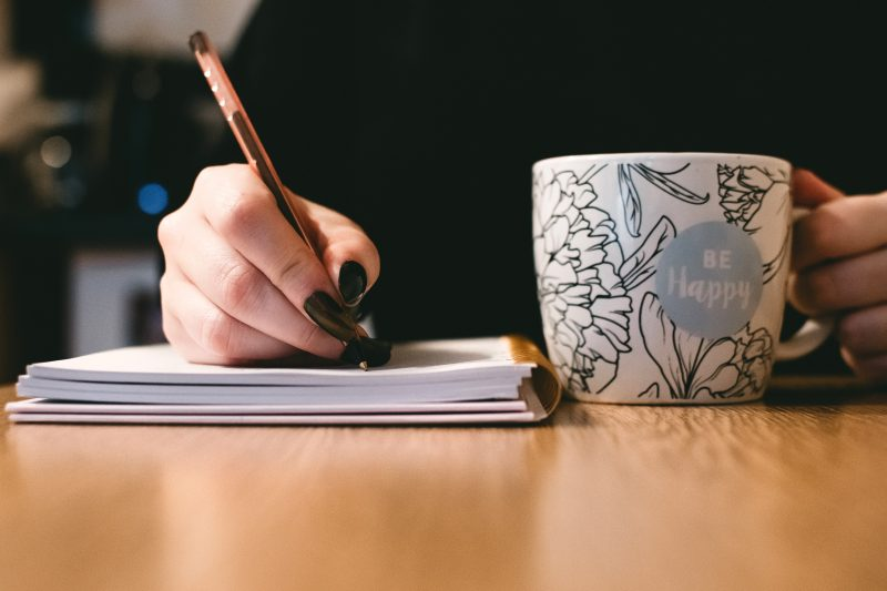 writing in notebook while drinking coffee | good copywriting