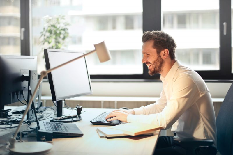 smiling while working at a desk | improve email marketing