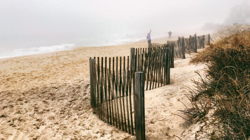 geofencing for marketing | people on beach behind fence