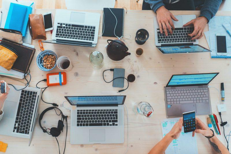 people working at communal table   DIY websites