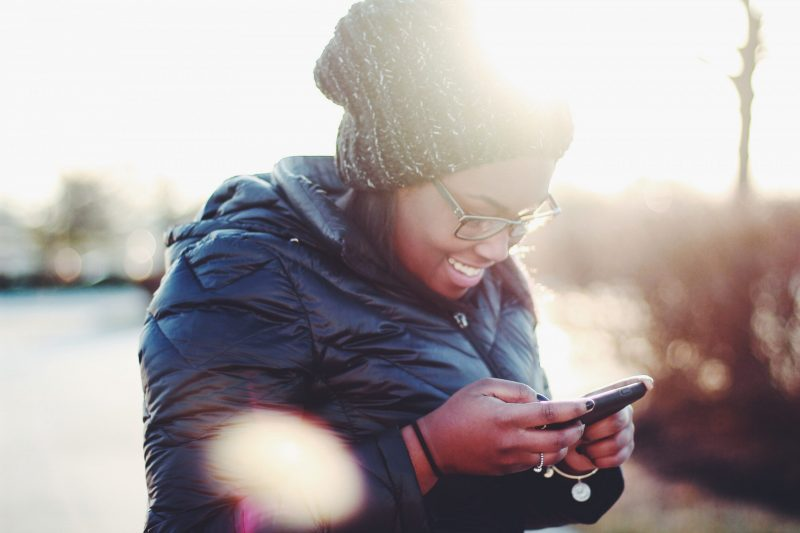 woman smiling while using smartphone | social media engagment
