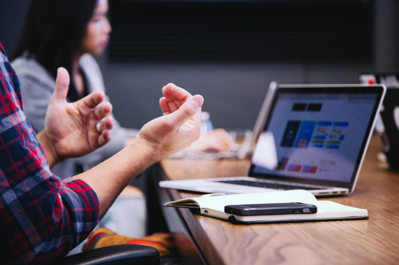 marketing strategy|person gesturing while sitting at a table with laptop at meeting